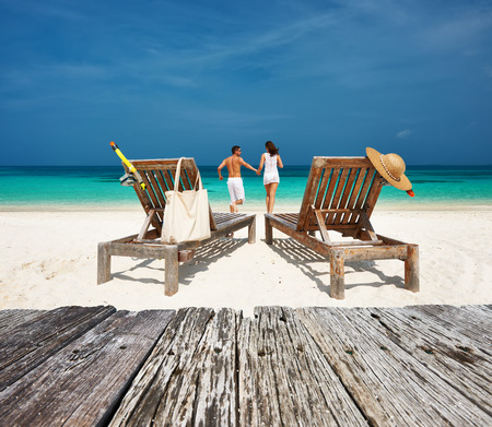 travel destination: Couple in white relax on a tropical beach at Maldives