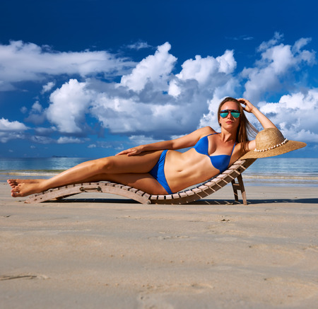 Woman in bikini lying on tropical beach at Seychelles photo