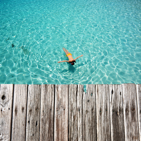Woman snorkeling in crystal clear turquoise water at tropical beach photo