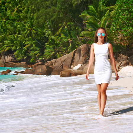 tree  forest: Woman wearing dress on beach Anse Intendance at Seychelles, Mahe