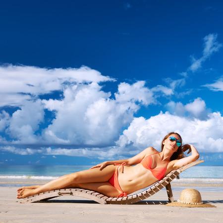 Woman in bikini lying on tropical beach at Seychelles photo