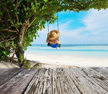 swinging: Woman in blue dress swinging at tropical beach Stock Photo