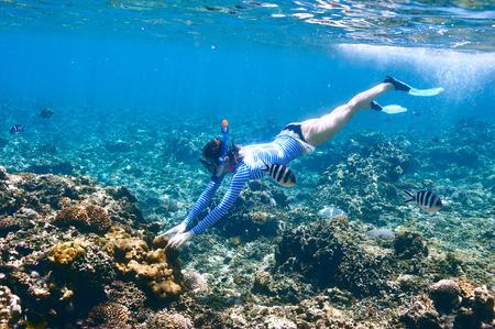 arrecife: Mujer con snorkel máscara en agua clara