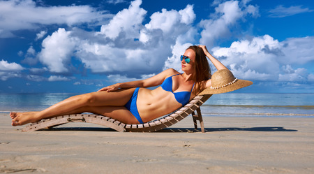 young girl bikini: Woman in bikini lying on tropical beach at Seychelles Stock Photo
