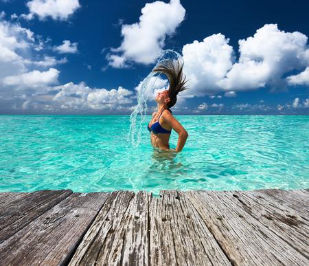 Woman Spritzwasser mit ihren Haaren in den Ozean