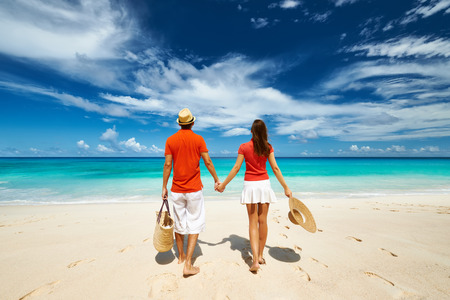 vacation destination: Couple relaxing on a tropical beach Anse Intendance at Seychelles, Mahe.