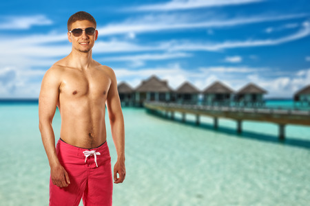 Man on beach with water bungalows at Maldives. Collage. photo