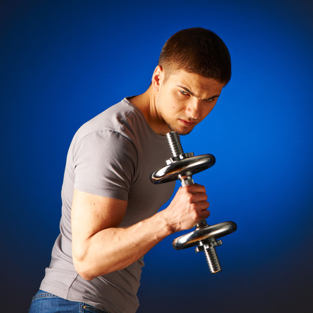 strong arm: Man working out with dumbbells on blue background