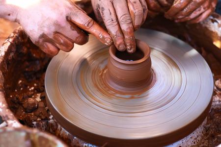 ollas de barro: Manos que trabajan con la arcilla en la rueda de la cerámica