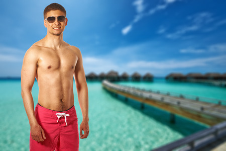 bungalows: Man on beach with water bungalows at Maldives. Collage. Stock Photo