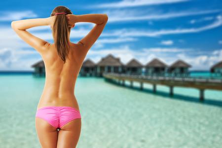 seins nus: Femme aux seins nus sur la belle plage avec bungalows sur pilotis � Maldives. Collage.