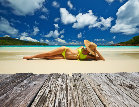 Vrouw in gele bikini liggend op tropisch strand op de Seychellen Stockfoto