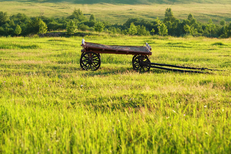 wagon wheel: Rural landscape with old wooden cart Stock Photo