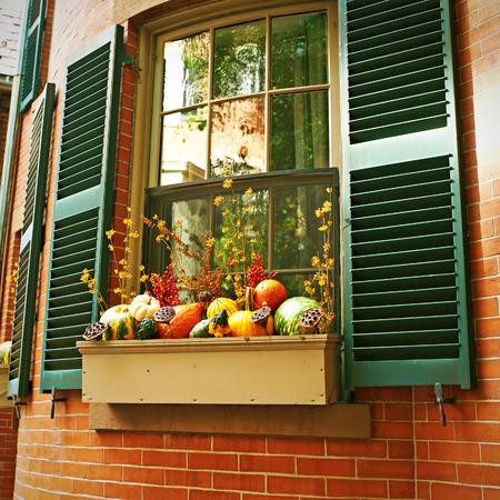 Pumpkins near house window during Halloween season
