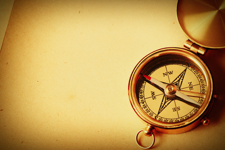 Antique brass compass over old map background