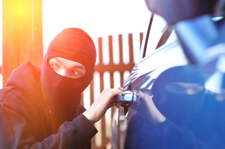 to steal: Young man in mask trying to steal a car
