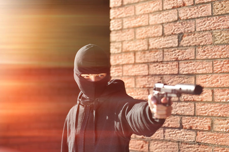 hitman: Gunman in black mask holding gun with silencer