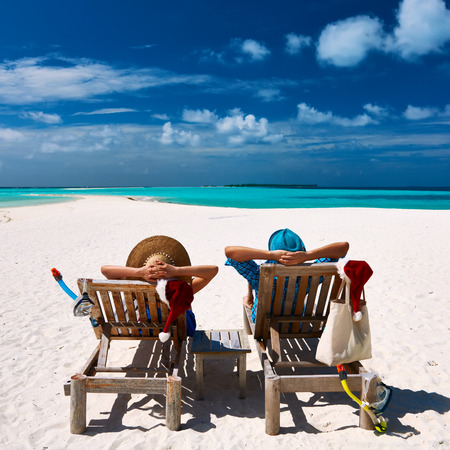 lounge chairs: Couple relax on a tropical beach at christmas Stock Photo