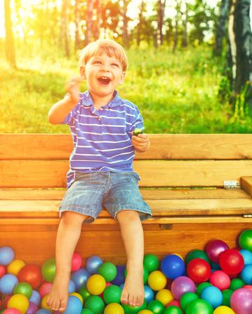 niños felices: Niño feliz que juega en coloridas bolas de plástico de alta vista del patio