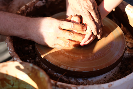 guiding: Potters hands guiding childs hands to help him to work with the pottery wheel