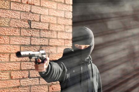 silencer: Gunman in black mask holding gun with silencer