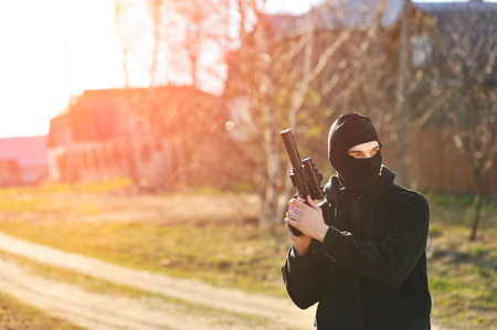 gunman: Gunman in black mask holding gun with silencer