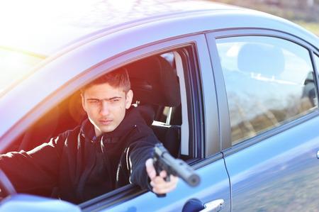 gunman: Gunman in car holding gun with silencer