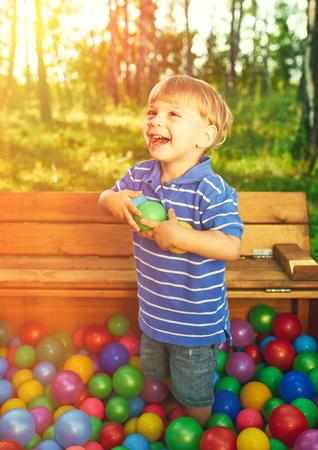 bola de billar: Niño feliz que juega en coloridas bolas de plástico de alta vista del patio