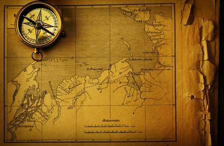 old fashioned: Antique brass compass over old map