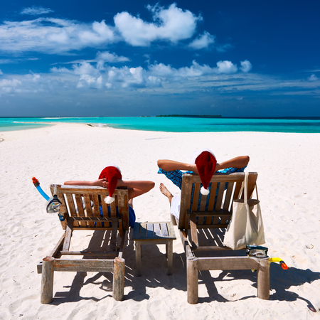 women sitting: Couple relax on a tropical beach at christmas Stock Photo