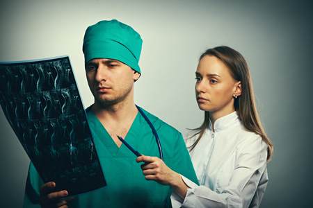 surgeons: Medical doctors team with MRI spinal scan portrait against grey background