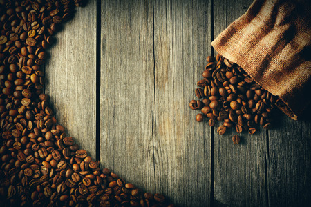 burlap background: Coffee beans and bag over wooden background Stock Photo