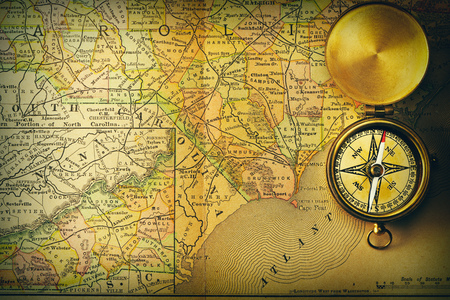 old fashioned: Antique brass compass over old XIX century map