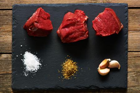 dark grey slate: Raw beef filet mignon meat over slate