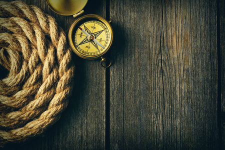 compass: Antique brass compass and rope over wooden background