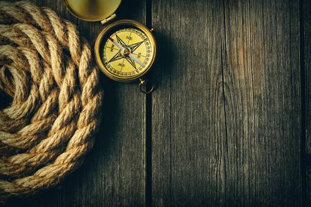 brujula: Compás de cobre amarillo antiguo y cuerda sobre fondo de madera