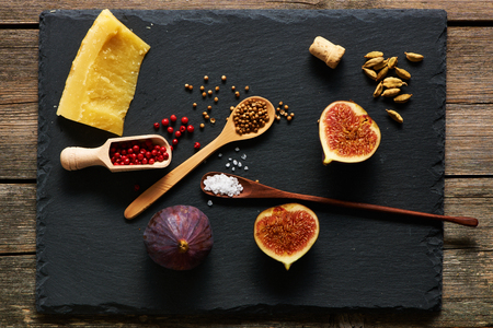 chopping board: Spices, cheese and figs over slate