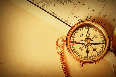 traverse: Antique brass compass over old Alaska map Stock Photo