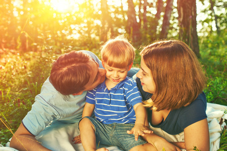 Happy family outdoors, father, mother and son photo