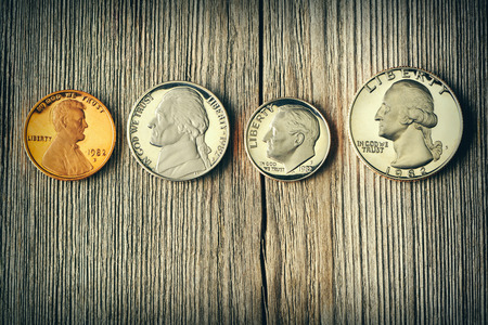 uncirculated: Four US cent coins over wooden background Stock Photo