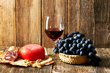 plank: Fresh grapes, cheese and red wine on old wooden table