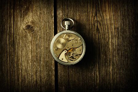 reloj: Mecanismo del mecanismo sobre fondo de madera Foto de archivo