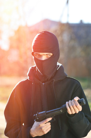 the silencer: Gunman in black mask holding gun with silencer