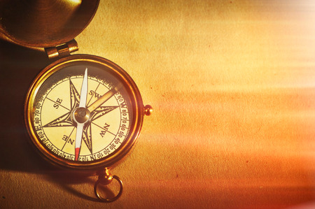 magnetic north: Antique brass compass over old paper background