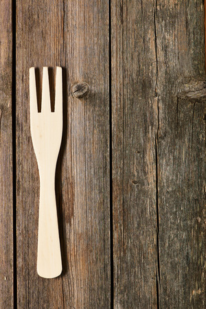 grunge cutlery: Wooden fork on rustic background