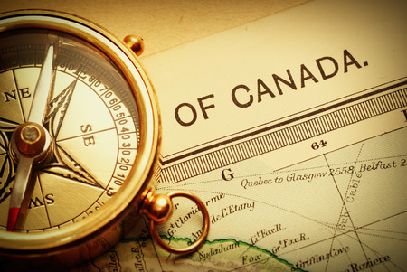map compass: Antique brass compass over old Canadian map background