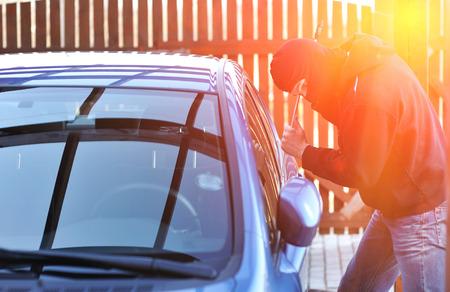 robo de autos: Hombre joven en máscara tratando de robar un coche Foto de archivo