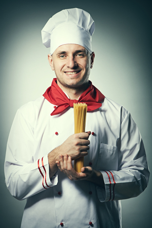 cook: Male chef holding pasta against grey background Stock Photo