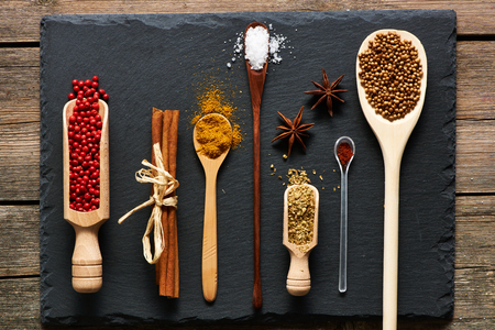 natural stone: Spices in wooden utensils over slate