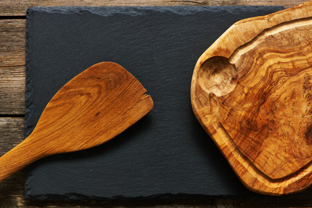 Olive wood cutting board and spatula over slate